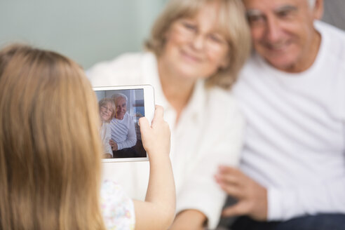 Little girl photographing her grandparents with digital tablet at home - WESTF019166