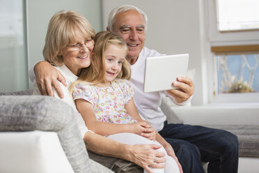 Senior couple and granddaughter looking at digital tablet at home - WESTF019163