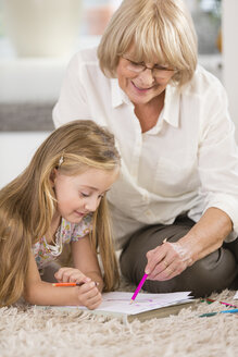 Senior woman and granddaughter painting with coloured pencils - WESTF019160