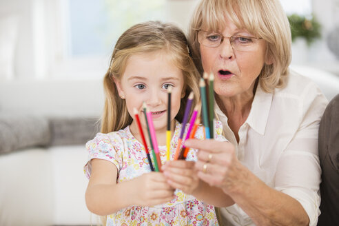 Senior woman and granddaughter showing coloured pencils - WESTF019157