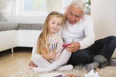 Senior man and granddaughter tinkering at home - WESTF019154