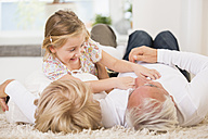 Senior couple and granddaughter lying on the floor at home - WESTF019148