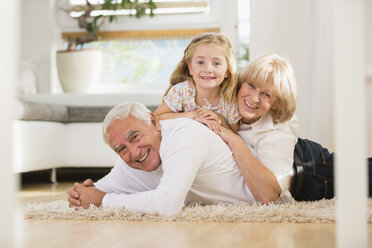 Family portrait of senior couple and granddaughter lying on the floor at home - WESTF019145