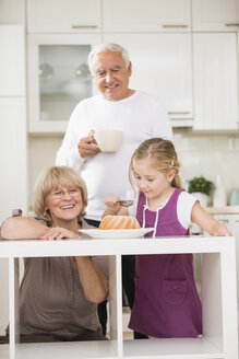 Senior couple with granddaughter in kitchen - WESTF019142