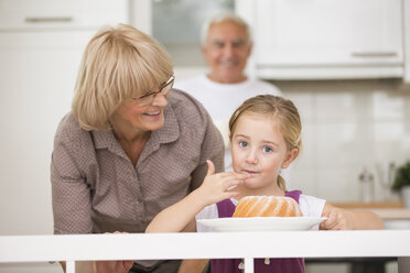 Senior couple with granddaughter in kitchen - WESTF019139