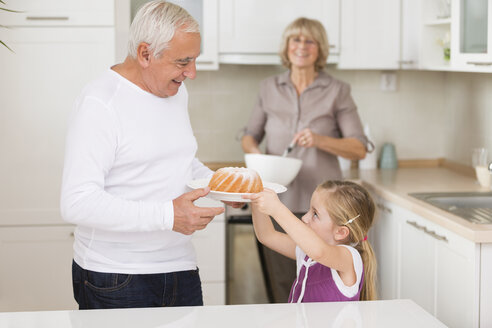 Senior couple with granddaughter in kitchen - WESTF019136