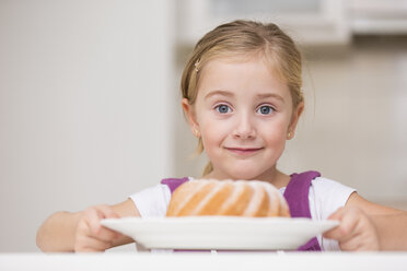 Portrait of smiling little girl holding plate with ring cake - WESTF019133