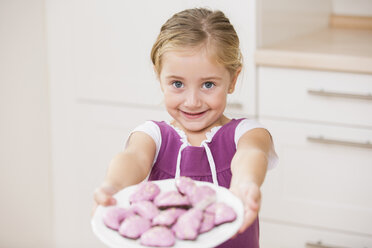 Portrait of smiling little girl holding plate of pink cookies - WESTF019130