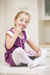 Portrait of smiling little girl sitting on a table eating pink cookies - WESTF019127