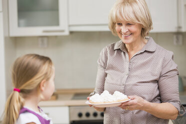 Portrait of senior woman and granddaughter with dish of waffles - WESTF019124