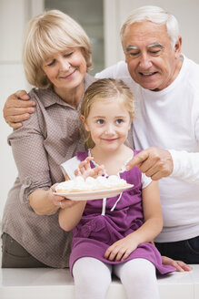 Portrait of senior couple with granddaughter in kitchen - WESTF019109