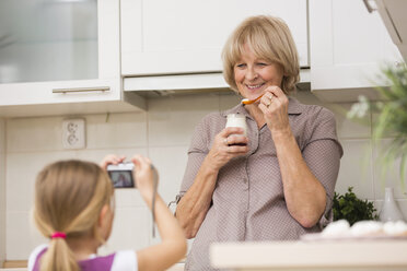 Little girl photographing her grandmother in kitchen - WESTF019112