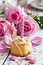 Muffin with lighted birthday candle, baking decor and pink roses on table - CSF021068