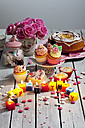 Muffins, birthday cake, cup cakes, roses, lighted birthday candles and baking decor on table - CSF021074