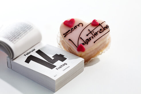 Petit four and tear-off calendar showing date of Valentine's day on white ground - CSF021084