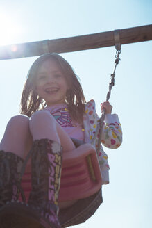 Portrait of smiling little girl on swing - SARF000423