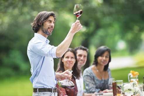 Man tasting red wine on a garden party - ABF000546
