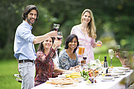 Man toasting with red wine on a garden party - ABF000582