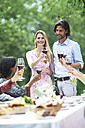 Couple holding glasses of red wine on a garden party - ABF000583
