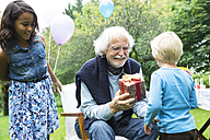 Grandfather receiving gifts on birthday party in garden - ABF000563