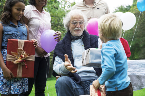 Grandfather receiving gifts on birthday party in garden - ABF000594