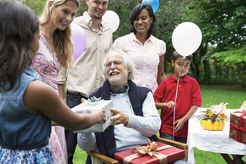 Grandfather receiving gifts on birthday party in garden - ABF000595