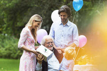Grandfather receiving gifts on birthday party in garden - ABF000597