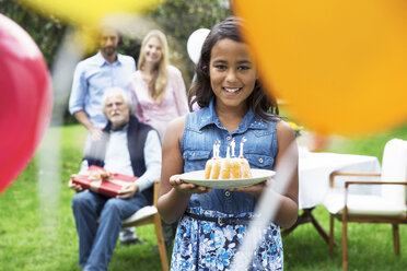 Girl in garden holding birthday cake - ABF000569