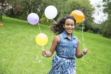 Smiling girl holding balloons in garden - ABF000575