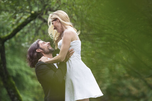 Happy groom lifting up bride in garden - ABF000576
