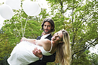Groom carrying bride in garden - ABF000526