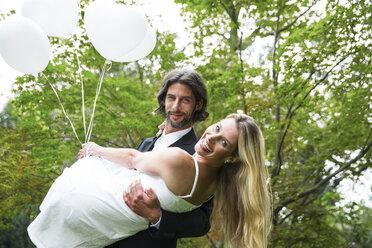 Groom carrying bride in garden - ABF000526
