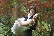 Groom carrying bride in garden - ABF000529