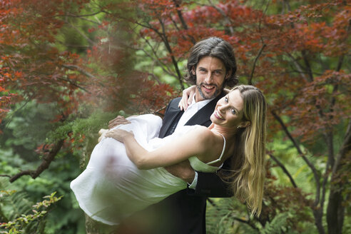 Groom carrying bride in garden - ABF000529
