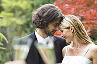 Happy bride and groom in garden - ABF000534