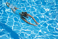 Italy, woman diving in swimmingpool - GWF002685