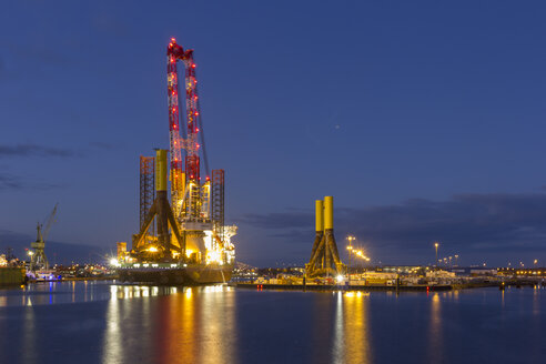 Germany, Bremerhaven, wind turbine installation vessel, tripods, blue hour - SJF000099