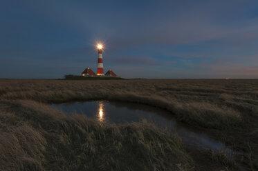 Germany, Schleswig-Holstein, North Sea Coast, View of Westerheversand Lighthouse at night - RJ000062