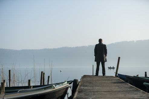 Man standing on wooden boardwalk watching at lake - PA000578