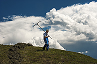 Austria, Radstadt, farmer on field, upcoming thunderstorm in the background - HHF004782