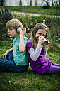 Boy and girl playing with tin can phone - SARF000409