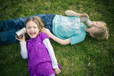 Boy and girl having fun with tin can phone - SARF000407