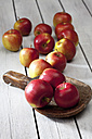 Braeburn apples on wooden shovel and grey wooden table - CSF021101