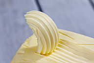 Piece of butter with butter curl, close-up - CSF021125