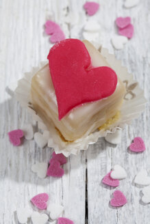 Petit four decorated with heart of marzipan on white wood - CSF021156