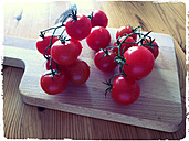 Vine tomatoes on a wooden board, studio - MYF000271