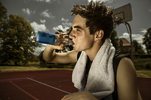 Portrait of young basketball player drinking water out of bottle - GCF000016