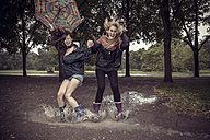 Two playful young women with umbrella jumping in puddle - GCF000004
