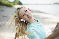 Young woman with headphones dancing on beach - LFOF000156