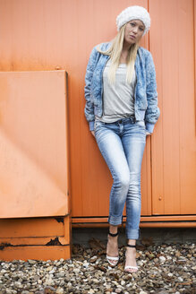 Fashionable blond young woman leaning at orange facade - LFOF000167